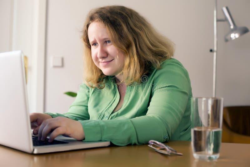 Ung kvinna med bärbar dator royaltyfri fotografi