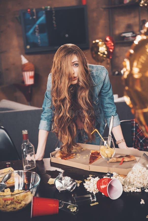 Ung kvinna med bakrusbenägenhet på den smutsiga tabellen efter parti royaltyfria bilder