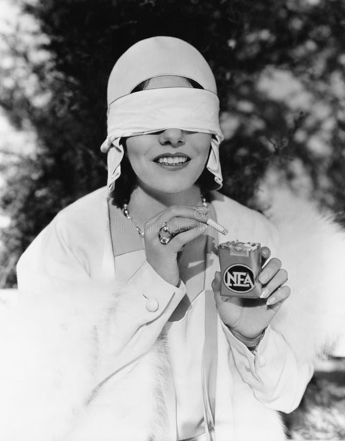 Ung kvinna med band för ögonen på ögon som ut tar en cigarett från en cigarettpacke (alla visade personer inte är längre uppehäll royaltyfri foto