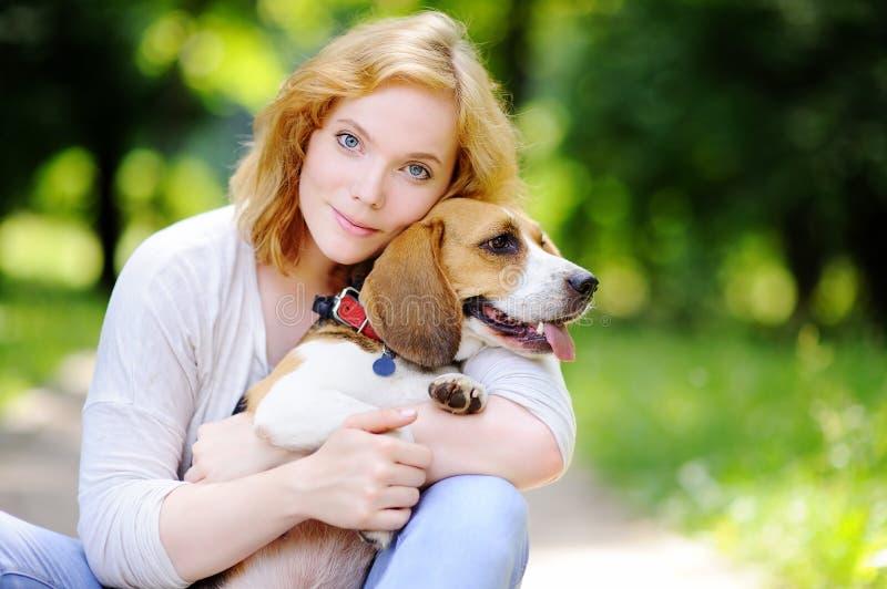 Ung kvinna med beaglehunden i parkera royaltyfri foto