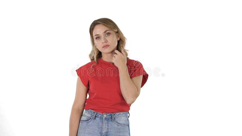 Ung kvinna med blont h?r i den r?da T-tr?ja som ser kameran som ?r k?nslol?s p? vit bakgrund fotografering för bildbyråer