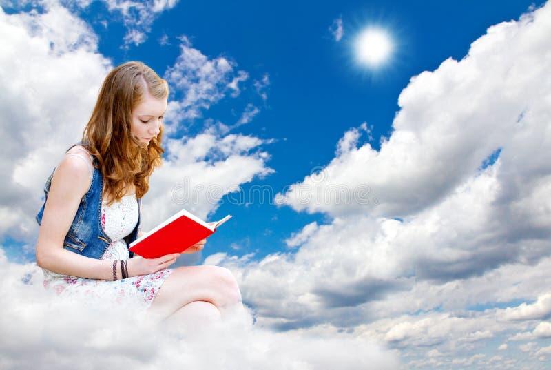 Ung kvinna med boken i himlen fotografering för bildbyråer