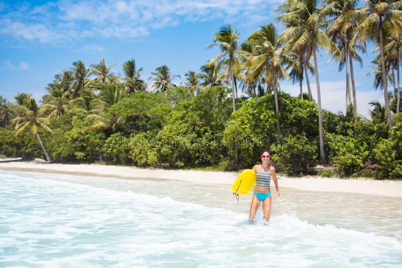 Ung kvinna med bränningbrädet på den tropiska stranden royaltyfri bild