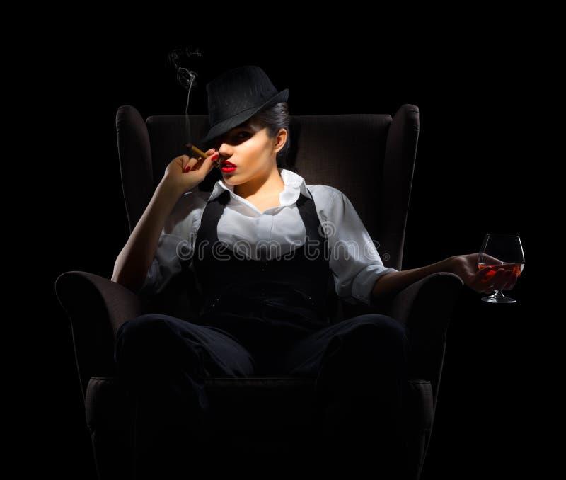 Ung kvinna med cigarr- och konjakexponeringsglas på stol royaltyfria bilder