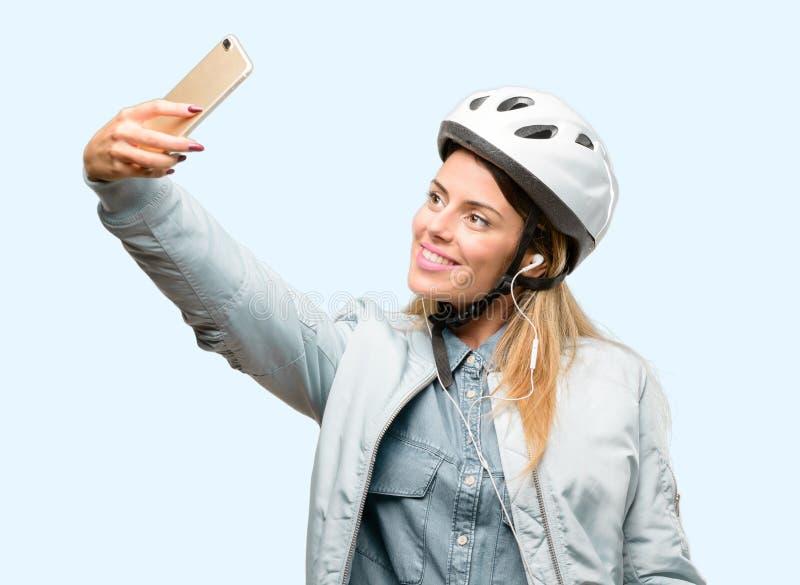 Ung kvinna med cykelhjälmen och hörlurar över blå bakgrund arkivfoto
