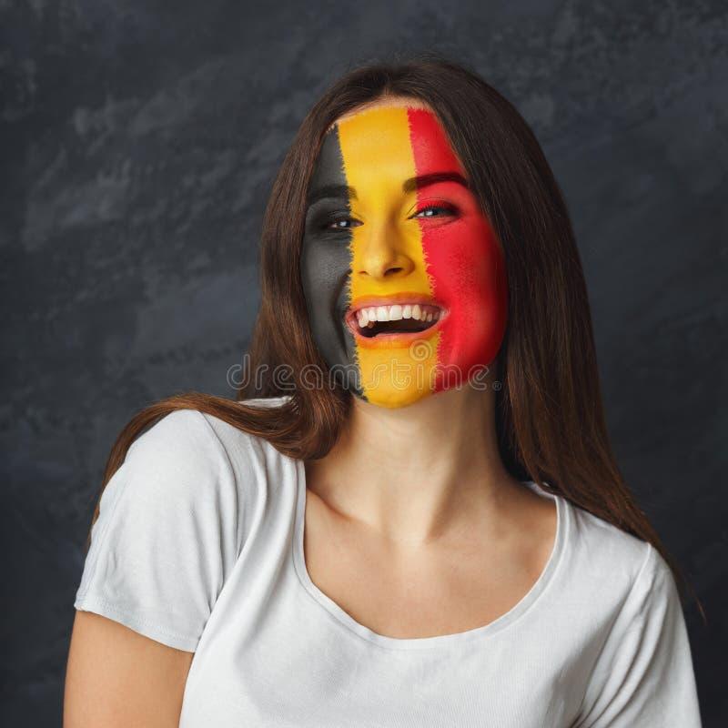 Ung kvinna med den Belgien flaggan som målas på hennes framsida arkivfoto