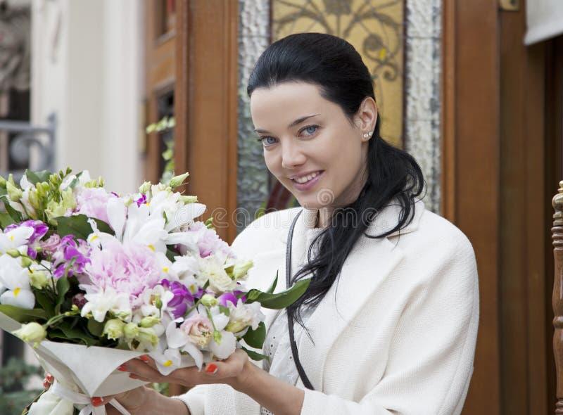 Ung kvinna med den blom- buketten arkivbild