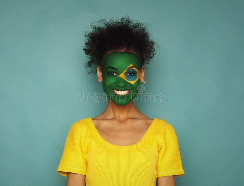 Ung kvinna med den Brasilien flaggan som målas på hennes framsida fotografering för bildbyråer
