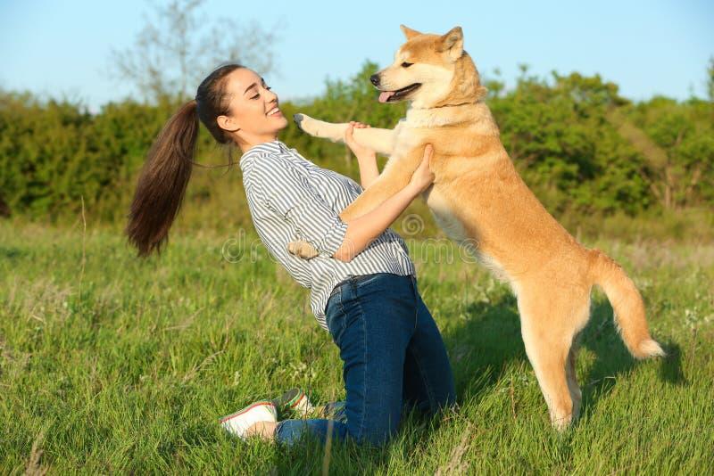Ung kvinna med den förtjusande Akita Inu hunden arkivbild