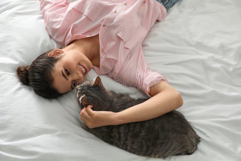 Ung kvinna med den gulliga katten på säng husdjur och ?gare arkivbild
