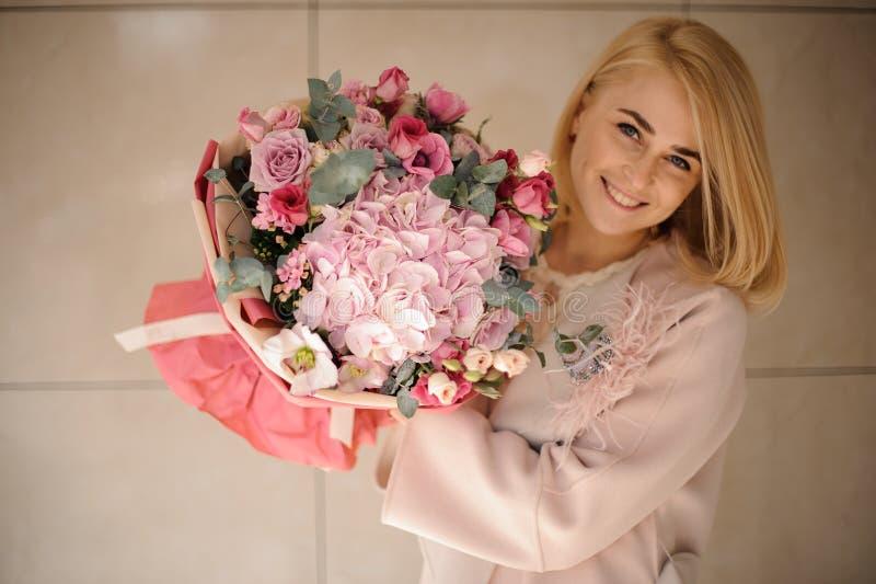 Ung kvinna med den härliga buketten av blommor arkivbilder