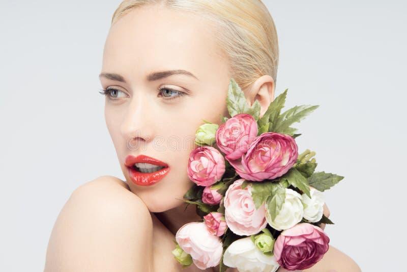Ung kvinna med den härliga framsidan och blommor hud royaltyfria bilder