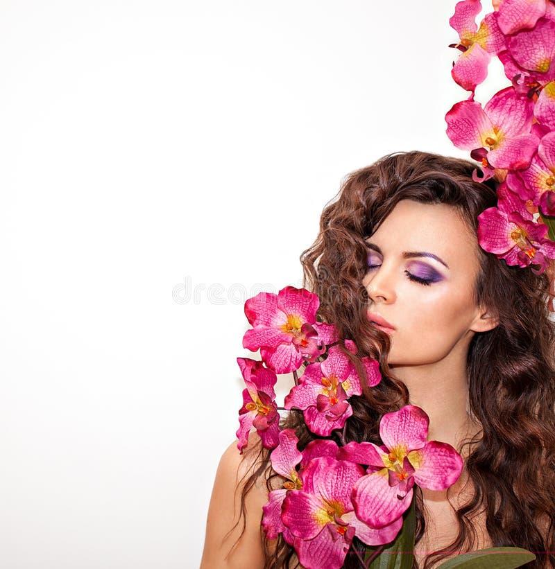 Ung kvinna med den härliga framsidan och nya blommor royaltyfri foto