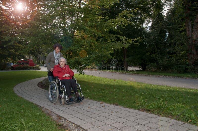 Ung kvinna med den höga kvinnan som sitter i rullstol royaltyfri fotografi
