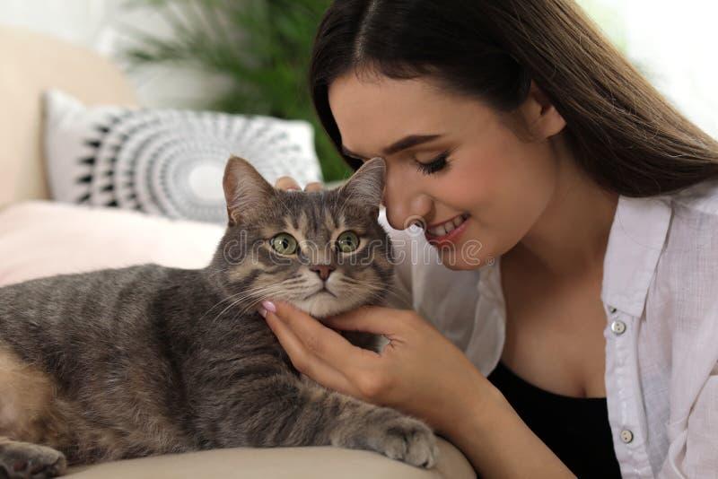 Ung kvinna med den hemmastadda gulliga katten husdjur royaltyfri foto
