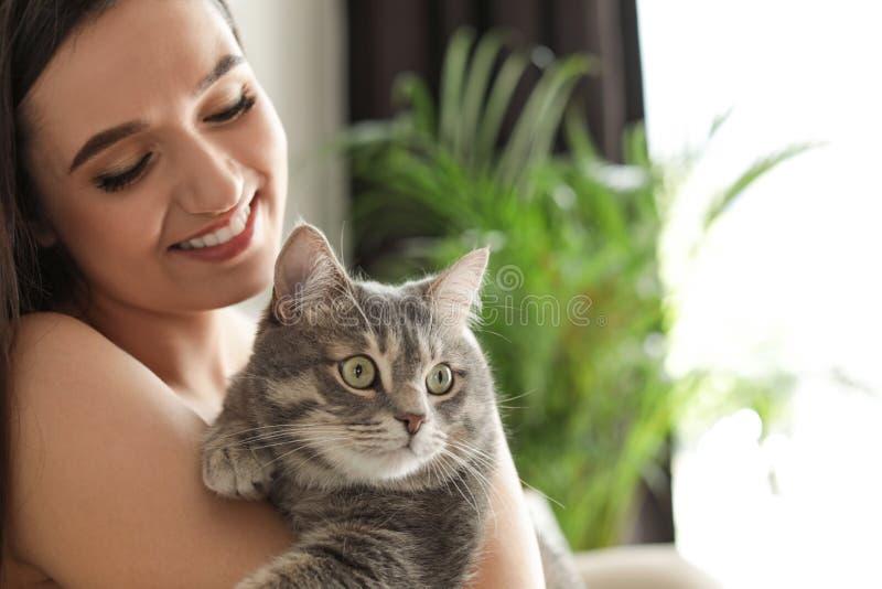 Ung kvinna med den hemmastadda gulliga katten husdjur och ?gare arkivfoton