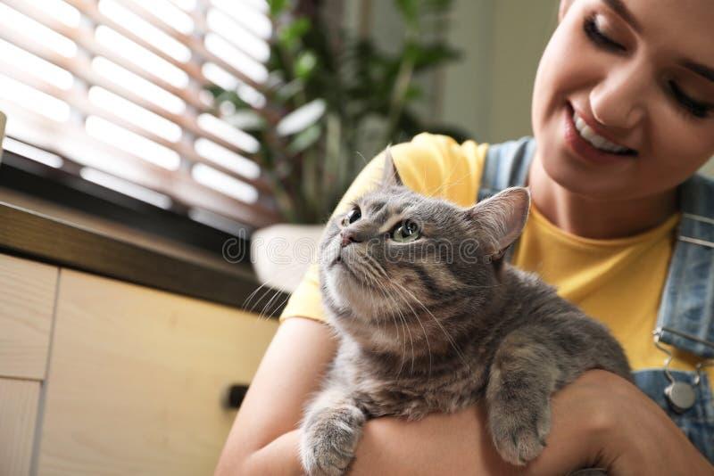 Ung kvinna med den hemmastadda gulliga katten husdjur och ?gare arkivbilder