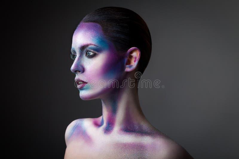 Ung kvinna med den idérika framsidamålarfärgståenden royaltyfria foton