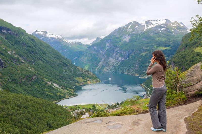 Ung kvinna med den mobila telefonen royaltyfri bild