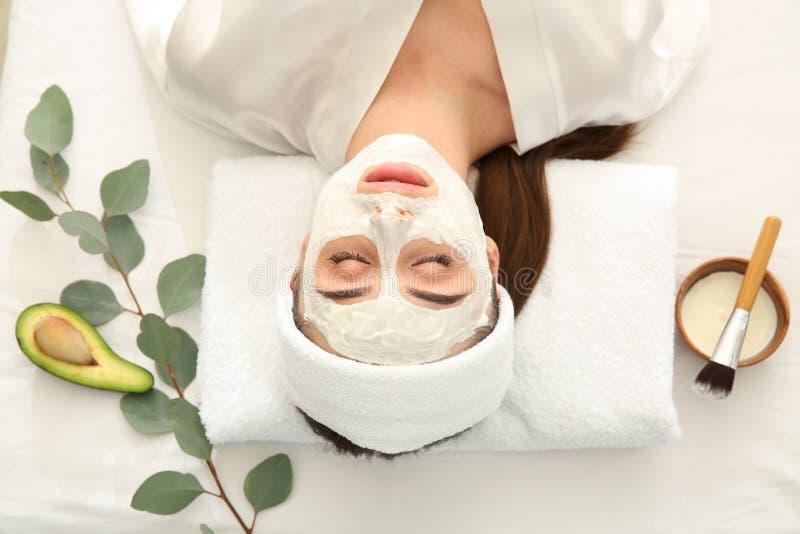 Ung kvinna med den naturliga ansikts- maskeringen i skönhetsalong royaltyfri fotografi