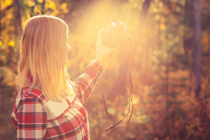 Ung kvinna med den retro fotokameran som tar selfieskottet royaltyfri bild