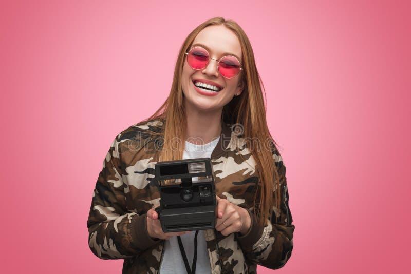 Ung kvinna med den retro kameran i studio arkivfoton