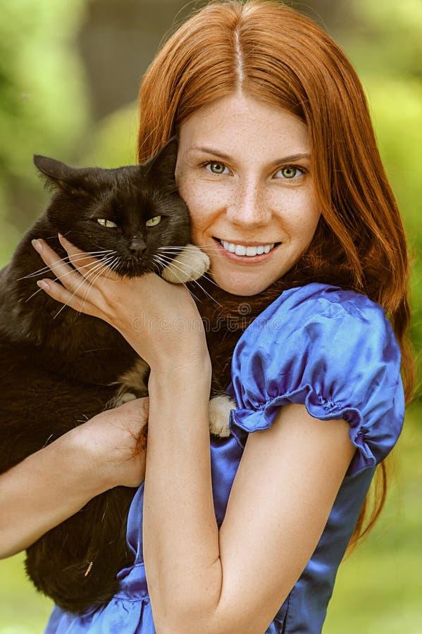Ung kvinna med den svarta katten royaltyfri fotografi