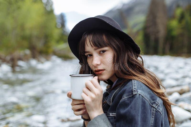 Ung kvinna med den utomhus- ståenden för kopp i mjukt soligt dagsljus royaltyfri bild