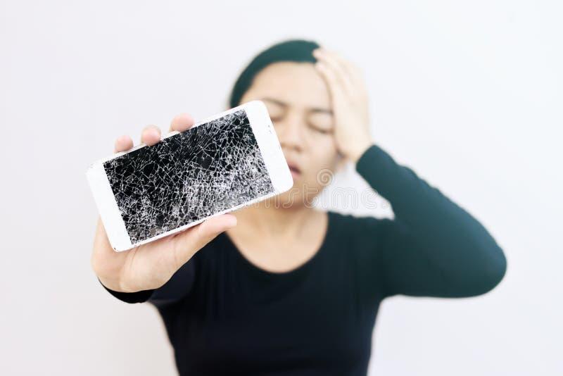 Ung kvinna med det besvärade uttryckt som rymmer hennes brutna telefon royaltyfri fotografi