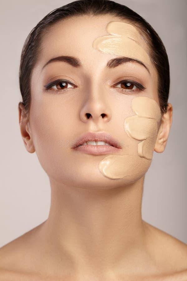 Ung kvinna med det kosmetiska fundamentet på en hud arkivfoton