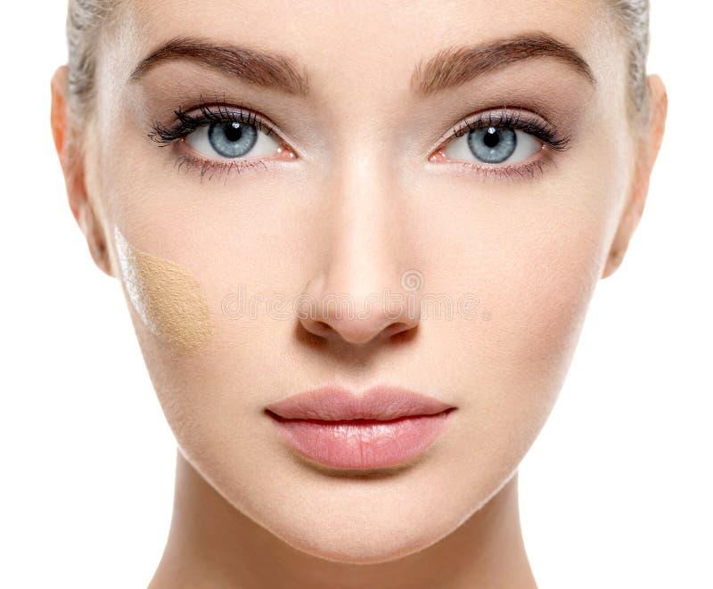 Ung kvinna med det kosmetiska fundamentet på hud arkivbild