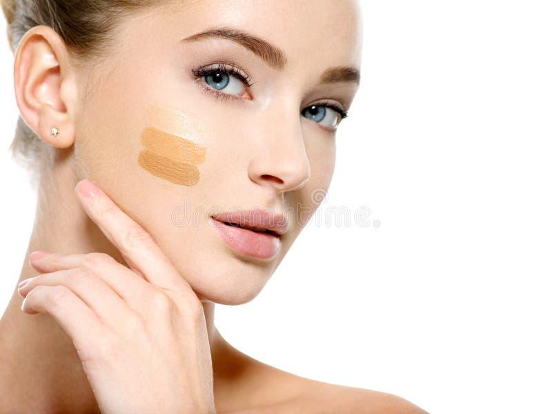 Ung kvinna med det kosmetiska fundamentet på hud royaltyfria foton