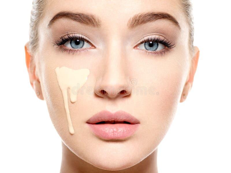 Ung kvinna med det kosmetiska fundamentet på hud arkivfoto