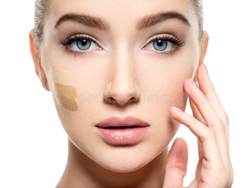 Ung kvinna med det kosmetiska fundamentet på hud royaltyfria bilder