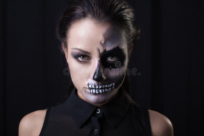 Ung kvinna med det skräckinjagande sminket som poserar på svart bakgrund royaltyfri bild