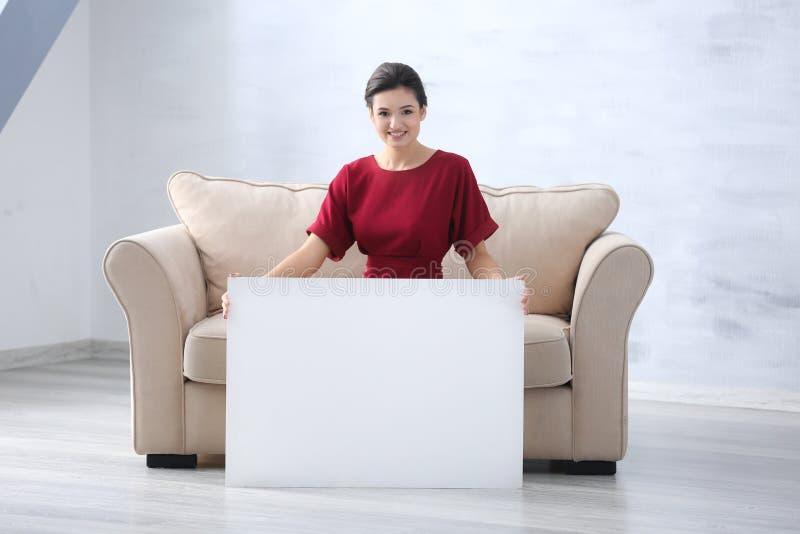 Ung kvinna med det tomma advertizingbrädet fotografering för bildbyråer