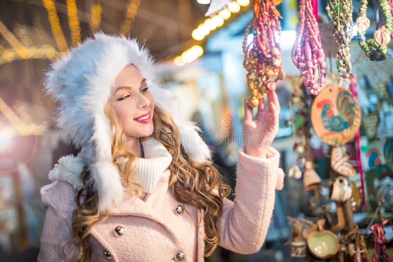 Ung kvinna med det vita pälslocket som beundrar tillbehör i Xmas-marknaden, kall vinterafton den härliga blondinkläder klädde vin arkivfoton