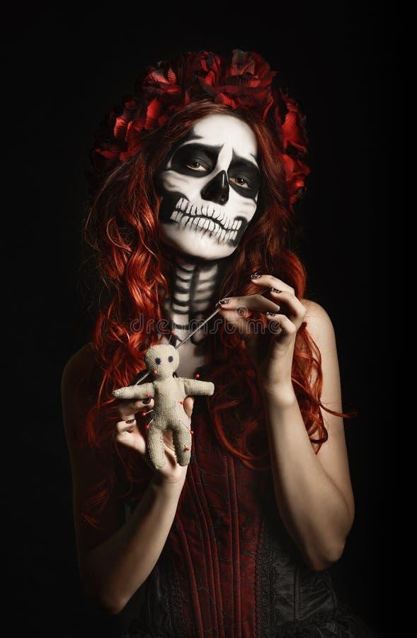 Ung kvinna med dockan för voodoo för calaveramakeup (sockerskalle) den genomträngande royaltyfri foto