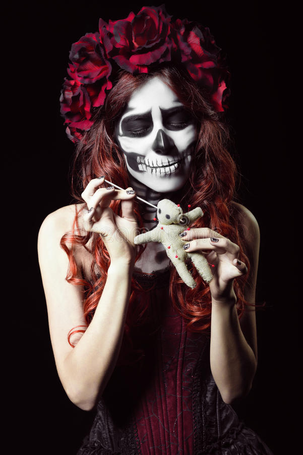 Ung kvinna med dockan för voodoo för calaveramakeup (sockerskalle) den genomträngande royaltyfri bild