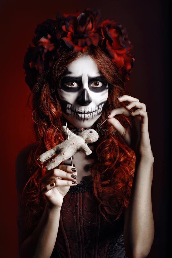Ung kvinna med dockan för voodoo för muertosmakeup (sockerskalle) den genomträngande royaltyfri fotografi