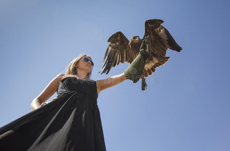 Ung kvinna med en örn arkivfoton