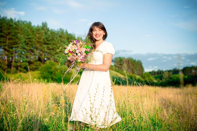 Ung kvinna med en bukett i handsnurr och dans i skogen och fälten royaltyfri fotografi