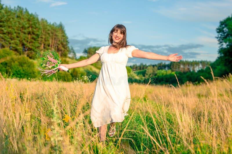 Ung kvinna med en bukett i handsnurr och dans i skogen och fälten fotografering för bildbyråer