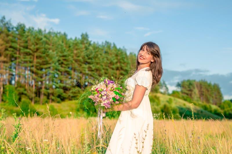 Ung kvinna med en bukett i handsnurr och dans i skogen och fälten royaltyfria bilder