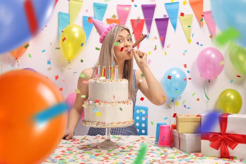 Ung kvinna med en födelsedagkaka som blåser ett partihorn royaltyfri fotografi