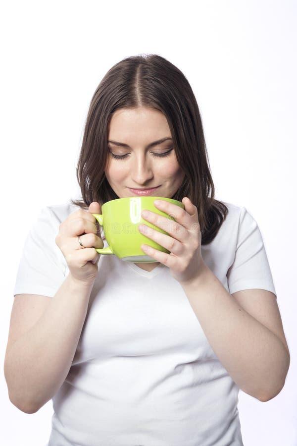 Ung kvinna med en grön kopp royaltyfria foton