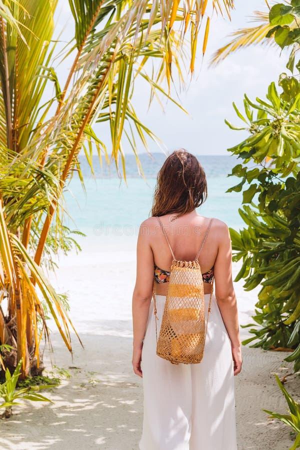 Ung kvinna med en handduk som g?r till stranden i en tropisk destination royaltyfri foto