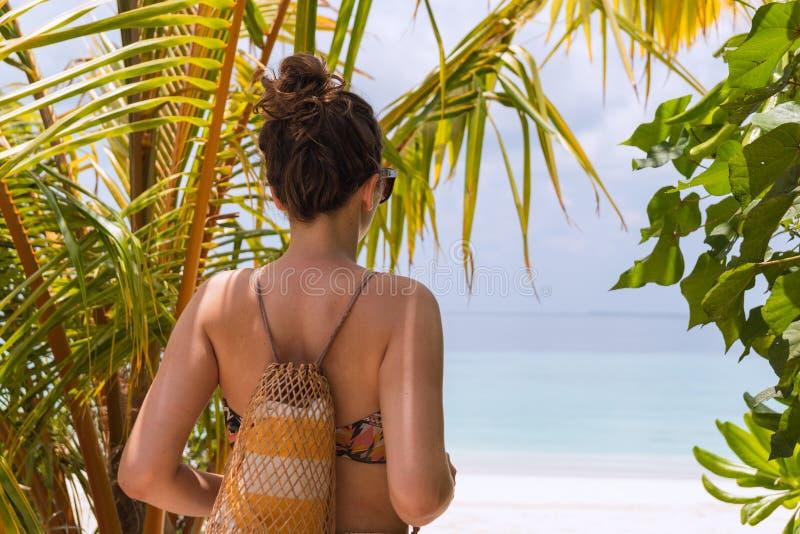 Ung kvinna med en handduk som g?r till stranden i en tropisk destination royaltyfri fotografi