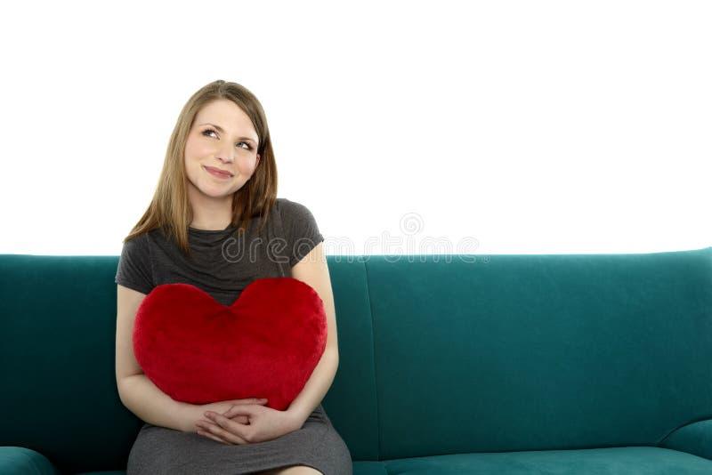 Ung kvinna med en hjärtakudde arkivfoto