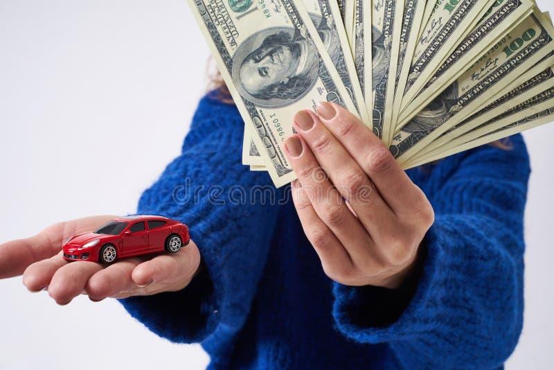 Ung kvinna med en leksakbil och pengar i hand royaltyfri foto